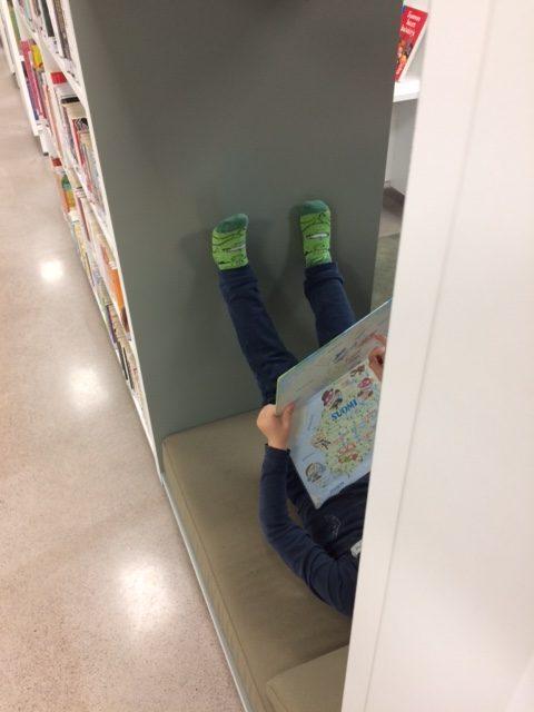 Lapsi makoilee sohvalla lukemassa kirjaa.