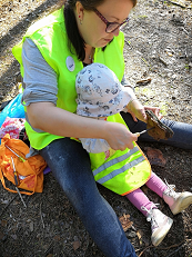 Lastenhoitaja tekee lapsen kanssa kaarnalaivaa.