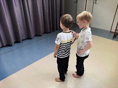 edessä oleva lapsi pitää silmät kiinni ja takana oleva pitää edessä olevaa olkapäästä kiinni ja ohjaa häntä.