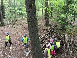 Lapset leikkivät risumajan sisällä ja ulkona.