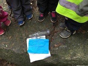4 lasta puoliympyrässä pullopostin ympärillä.