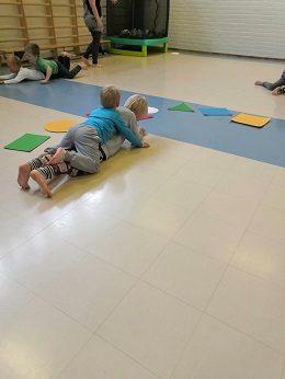 Jumppasalissa neljän lapsen pitää liikkua pareittain niin että toisen vatsa on kiinni lattiassa ja toisen vatsa parinsa selässä.