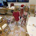 Neljä lasta leikkii lumella jonka he ovat tehneet paperisilpusta.
