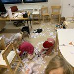 """Ryhmä lapsia valmistautuu """"lumisotaan"""" keräämällä paperisilppua lattialta."""