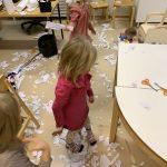 Lattia on valkoisenaan paperisilppua ja neljä lasta laikkii lumileikkejä niiden avulla.