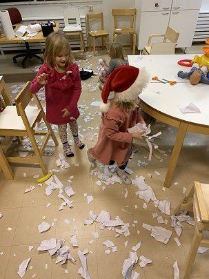 Kaksi lasta valmistautuu lumen eli paperisilpun heittämiseen