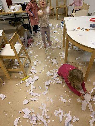 Lepset leikkivät lumisotaa. Paperisilppua on lattia valkoisenaan.