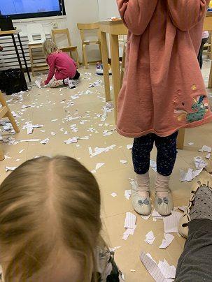 Kolme lasta kerää paperisilppua lattialta.