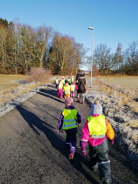 Lapsiryhmä ja kaksi aikuista kävelevät selkä kameraan päin aurinkoisessa säässä.