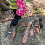 Lapsi esittelee keräämiään metsän aarteita: kaksi kiveä, erimallisia käpyjä, vahvan vihreitä männynoksia, erimallisia keppejä ja oksia.