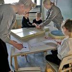 Aikuiset ja lapset rakentava bensatankkia pöydän ympärillä askartelumateriaaleista.