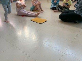 Lapset istuvat piirissä ja kannustavat kun yksi jouksee piiriä ympäri.