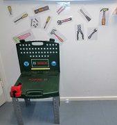 Pieni vihreä työkalupenkki ja sen takana seinällä kuvia erilaisista työkaluista.
