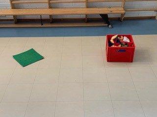 Vihreä merkkilaatta mistä pitää heittää hernepusseja punaiseen laatikkoon jumppasalissa.