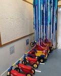 Autot ja mopot ovat rivissä parkissa seinän vieressä ja katosta roikkuu sinisistä silkkipapereista tehty vesiputous.