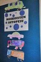 """Kyltissä teksti """"Moikoisten autopesula"""" ja kylttiä koristaa lasten itse piirtämät ja väkirrämät kolme autoa."""