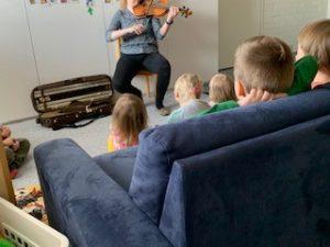 Aikuinen soittaa päiväpiirissä viulua ja lapset katsovat ja kuuntelevat etualalla.