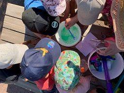Lapset ulkona kokoontuneet retkeilypöydän ääreen tekemään saippuakuplalientä.
