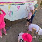 Iso paperi on ripustettu ulkona palloseinään ja siihen ryhmä lapsia maalaa vesiväreillä erilaisia kuvia.