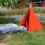 Tiipii-teltasta pilkistää lasten jalkoja. kengät ovat teltan ulkopuolella etualalla.