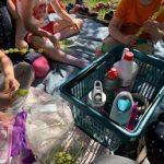 Viisi lasta istuvat viltillä ja heidän edessään on ostoskori jossa on juomapulloja. Lapset laittavat varrastikkuihinn viinirypäleitä ja vaahtokarkkeja.