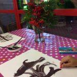 Lapsi värittää pihlajanmarjatyötä.
