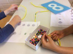 Lapset pujottelevat mallin mukaan hamahelmiä keltaiseen piipunrassiin.