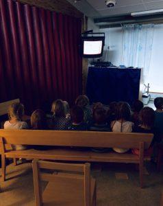 Lapsia katsomassa elokuvaa päiväkodin salissa.