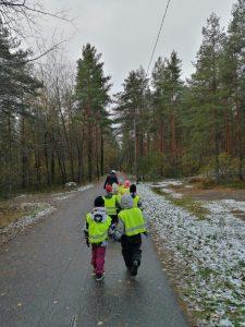 lapset kävelemässä kirjastolle metsäistä kävelytietä pitkin