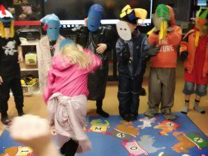 lapsi paljastamassa itsensä maskin takaa, muita lapsia taustalla