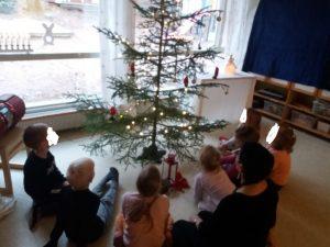 Lapsia kerääntynynyt ihastelemaan kuusen ympärille sen koristeita ja valoja