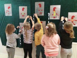 Lapset laittavat tekemiään joulukoristeita esille seinälle, tonttuaskartelut ja joulunauhaa