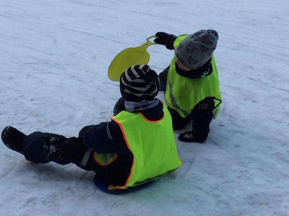 kaksi lasta lähdössä laskemaan liukurilla alas pulkkamäkeä