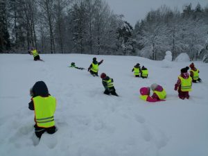 lapsia kahlaa lumihangessa