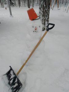 lumiukko lumilapio kädessä