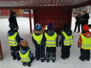 lapsia rivissä katsomassa grillin tulta yhdessä aikuisten kanssa
