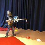 lapsi ritarileikeissä miekan ja kypärän kanssa
