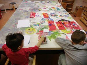 kaksi lasta piirtämispuuhissa