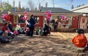 lapsia ja aikuisia päiväkodin pihalla juhlimassa stop kiusaamiselle -kampanjaa, ilmapalloja ja viirejä koristeena
