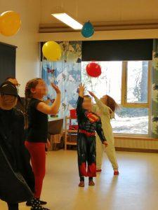 lapset pomputtelevat ilmapalloja ilmpaan