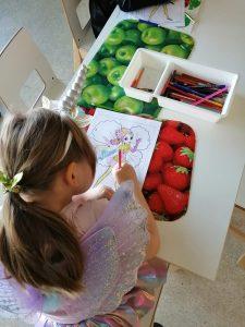 tyttö värittää värityskuvaa keijusta