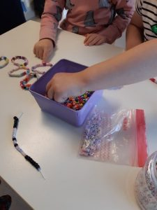 lapset pujottelemassa helmiä rannekoruksi