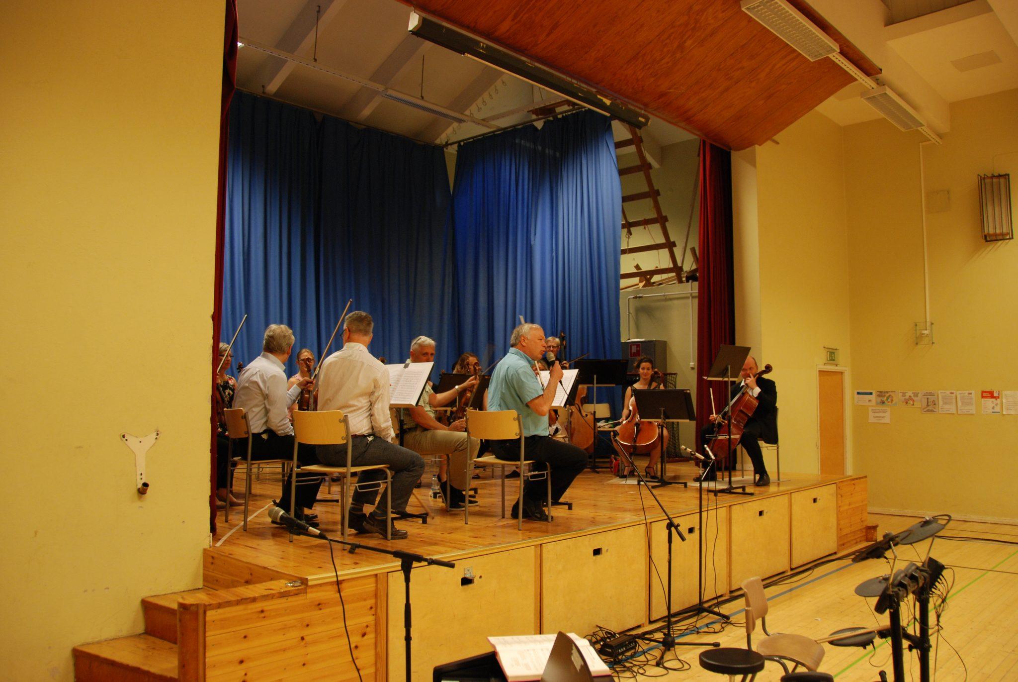 Orkesteri soittaa koulun liikuntasalin lavalla.
