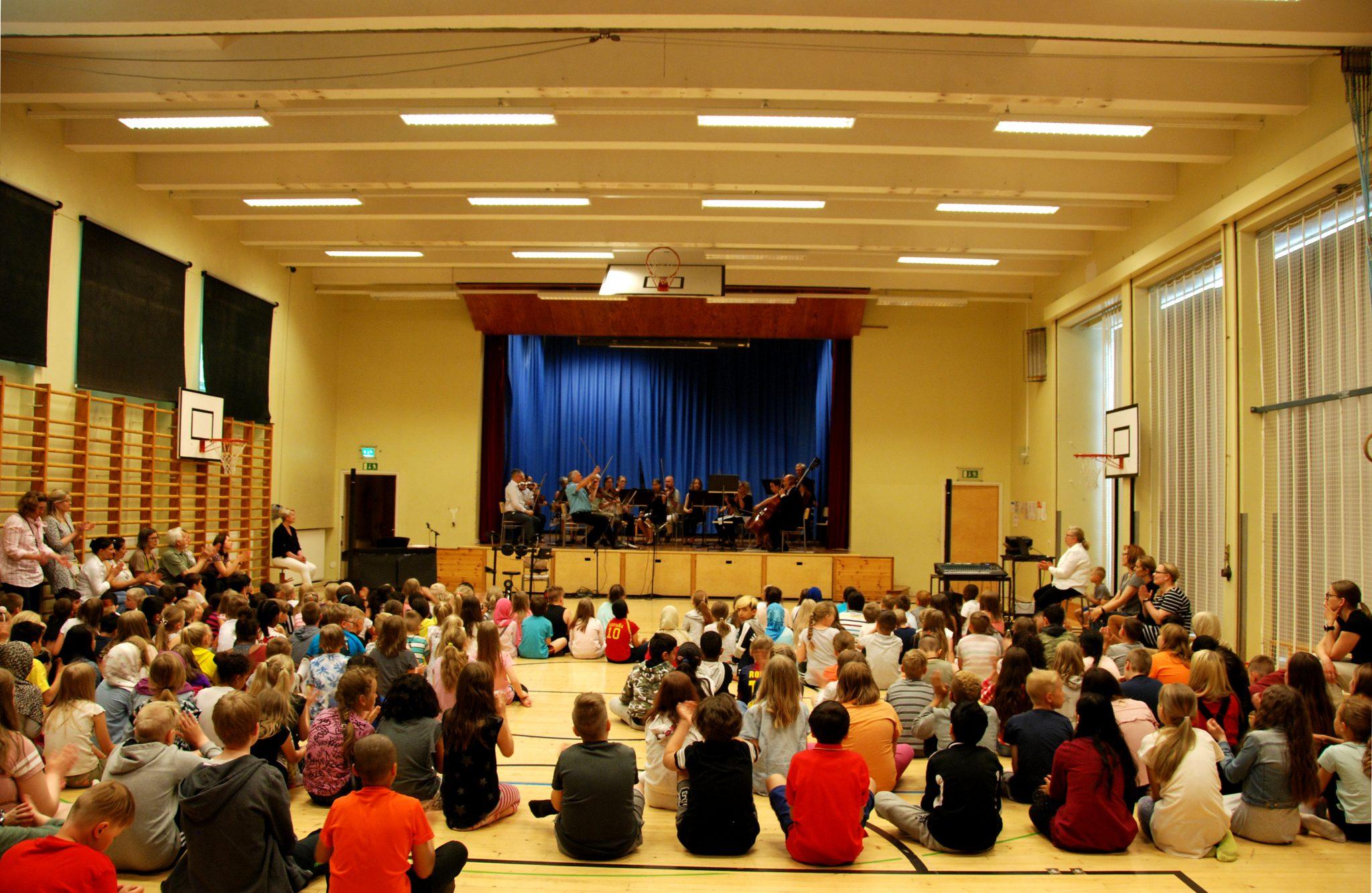 Kuvassa orkesteri esiintyy oppilaille koulun liikuntasalissa.