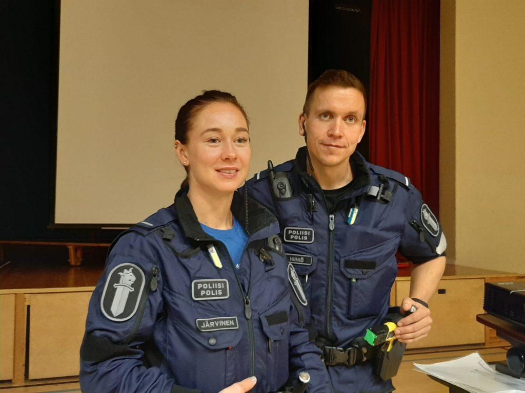 Kuvassa kaksi poliisia luennoivat koulun salissa.