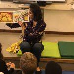 Taiteilija lukee kirjaansa oppilaille