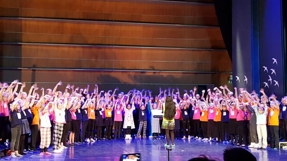 Kaikki alakoulun musiikkiluokkalaiset Sigyn -salin lavalla esiintymässä.