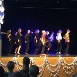 Oppilaita jonossa tanssimassa näyttämöllä.