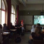 Hämärässä opetustilassa opettaja näyttää videota oppilaille.