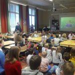 Oppilaat laulvat luokassa valkokankaalla näkyvää laulua.